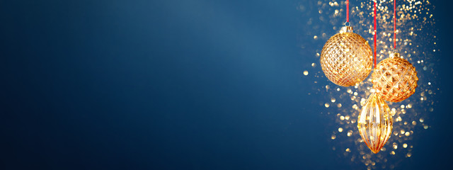 Three golden Christmas baubles hanging against the dark blue background with golden dust. New Year banner.