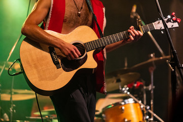 shirtless man playing guitar on stage, close-up view of male guitarist hands during night live music performance with drums in the background