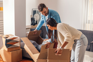 Smiling young couple move into a new home carrying boxes of belongings.