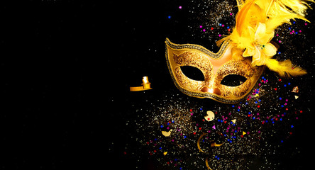 Masquerade mask on black background with sparkles. The concept of traditional holidays. Copy space