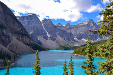 Iconic Canadian landscape, trip of a lifetime, Moraine Lake with it's glacier fed light blue turquoise waters and majestic peaks on a sunny day in the end of august, wilderness forest landscape.