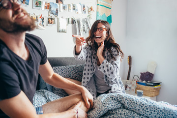 Young happy couple playing laughing on bed indoor home laughing