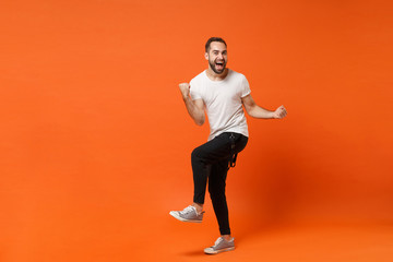 Joyful happy young man in casual white t-shirt posing isolated on orange wall background studio portrait. People sincere emotions lifestyle concept. Mock up copy space. Clenching fists like winner.