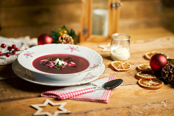 Traditional christmas red borscht on wooden table