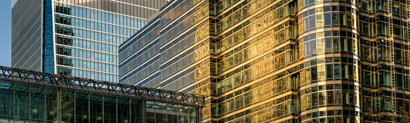 Modern city building architecture with glass fronts on a clear day at sunset in London, England panoramic