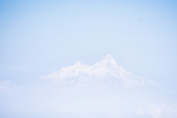 Beautiful shot of the Himalayas mountains in the distance with a blue sky in the background