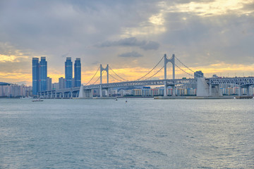 Scenic view of awesome sunset over modern bridge, sea and skyscrapers in Busan in South Korea. Beautiful summer cloudy look of evening in relax place in resort city of Republic of Korea