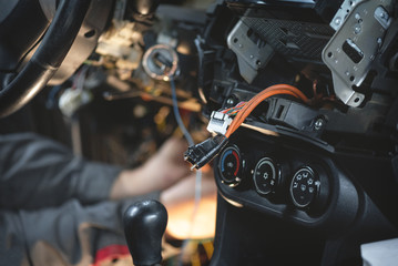 Auto electrician worker is installing a car alarm close up concept.