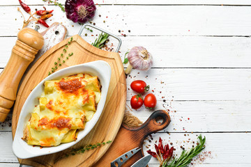 Cannelloni paste baked with meat, cream sauce, cheese. Italian cuisine. Top view. Free copy space.