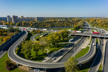 Aerial shot of a big freeway intersection in Warsaw, traffic going fast through many road flyovers. Warsaw, Poland. Drone shot at a highway with a clover junction with bridges and ramps, heavy traffic