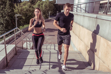 Beautiful athletic young fitness couple, man and woman, jogging on jump on stairs, summer fitness training in city, sportswear. Background stair steps trees. Speed is strength and stamina.