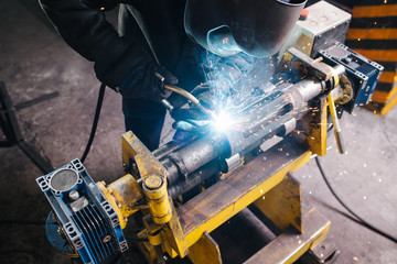 Hish angle image of a welder working on metal piece, fixed with industrial clamp