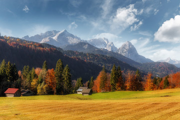 Awesome alpine highlands in sunny day. Sunny valley with Zugspitze mountain range and perfect sky on background. Beautiful autumn Landscape of Bavarian Alps, Germany, Europe.