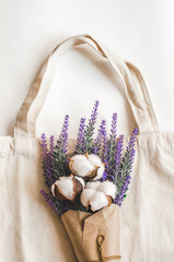 A bouquet of lavender and cotton-plant in paper on textile bag on white background