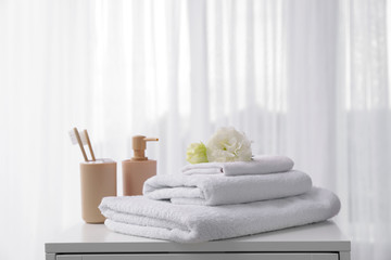 Soft towels, tooth brushes and soap on table near window
