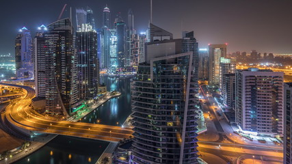 Aerial view of Dubai Marina residential and office skyscrapers with waterfront night timelapse