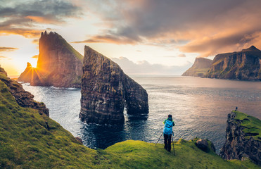 Photographer taking pictures to Drangarnir and Tindhólmur at sunset in the Faroe Islands