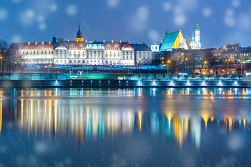 Old Town with reflection in the Vistula River during snowy evening blue hour, Warsaw, Poland.