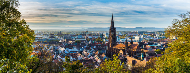 Germany, XXL panorama of city freiburg im breisgau skyline with cathedral muenster in old town in warm sunset light in romantic autumn season, aerial view above cityscape