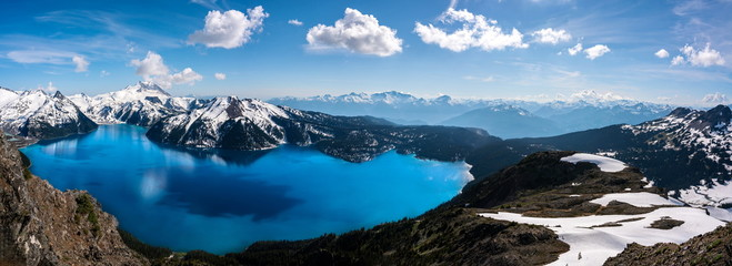 Panoramic view of mountains and turquoise coloured lake in Garibaldi provincial park, BC, Canada. snow mountains and blue sky.