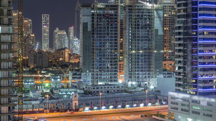 Aerial view of constructing with cranes night timelapse in Dubai.