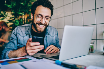 Positive caucasian hipster guy in eyewear laughing at content from social networks using mobile phone for browsing, cheerful male freelancer having fun during remote job  chatting on cellular.