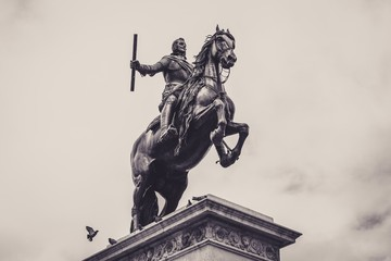 Low angle grayscale shot of a statue in front of the Royal Palace of Madrid