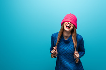 funny laughing woman in knitted sweater with pink hat on eyes, isolated on blue