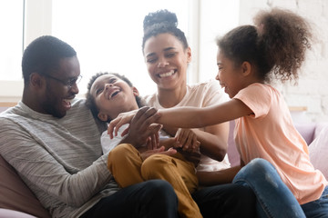 Overjoyed biracial family with kids have fun at home