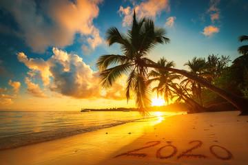 Szczęśliwego nowego roku 2020 koncepcja, napis na plaży. Wschód słońca nad morzem.