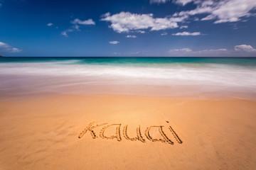 The word Kauai written on the sand of a beach in Kauai, Hawaii