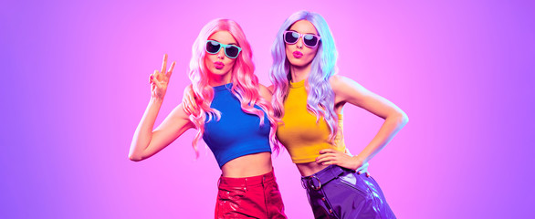 Gorgeous Disco Party girl with Having Fun, neon style. Pink Purple hairstyle. High Fashion. Two young beautiful model woman friends Dance, colorful neon Light. Night Clubbing.Pop Art fashionable Style