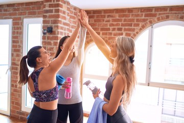 Young beautiful group of sportswomen smiling happy. Standing highing five with smile on face after class of yoga at gym