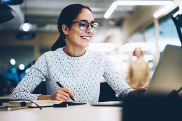 Cheerful businesswoman excited with accomplished project successfully monitoring news online via netbook, smiling female administrative manager happy about increasing company income making report
