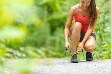 Fitness girl getting ready to run exercise outside lacing running shoes on run path in forest. Happy Asian woman exercising outdoors.