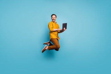 Full size photo of funky man feel rejoice emotions jump use laptop search social media online black friday discounts wear casual style clothing isolated over blue color background