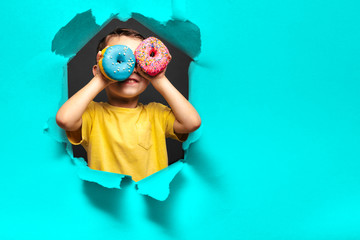 Happy cute boy is having fun played with donuts on black background wall.