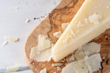 Pecorino romano, hard italian sheep milk cheese on wooden cutting board, selective focus