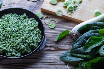Vegan dish, spinach risotto in cast iron skillet
