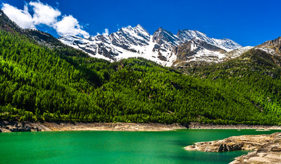 Green lake in Gran Paradiso Italian alps mountains in Graian Alps in Piedmont, Italy with snow capped peaks.