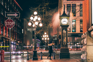 The famous Steam Clock in Gastown in Vancouver city with cars light trails at night