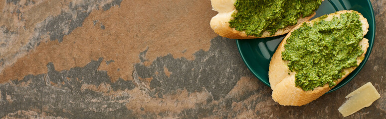 top view of baguette slices with pesto sauce on plate near parmesan on stone surface, panoramic shot