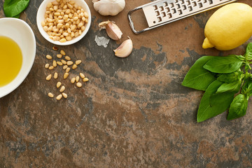 top view of pesto sauce ingredients and grater on stone surface