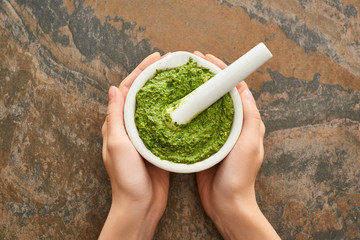 cropped view of woman holding bowl with pesto sauce on stone surface