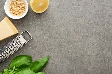 top view of pesto sauce raw ingredients and grater on grey surface