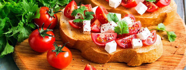 Traditional Italian bruschetta with tomatoes, cheese and herbs, border.