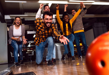 Group of friends enjoying time together laughing and cheering while bowling at club.