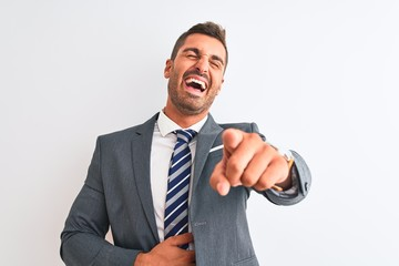 Young handsome business man wearing suit and tie over isolated background laughing at you, pointing finger to the camera with hand over body, shame expression