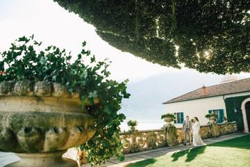 Villa Balbianello wedding photoshoot beautiful couple bride and groom long veil and white dress on mountains background lake Como Italy ceremony luxury beautiful sunny day