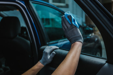 Worker cleaning car window after applying tinting foil